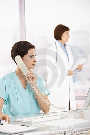 Assistant taking phone call, doctor in background