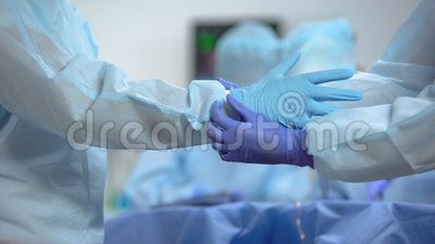 Assistente che indossa guanti chirurgici principali, prima di operare in una stanza d'ospedale sterile archivi video