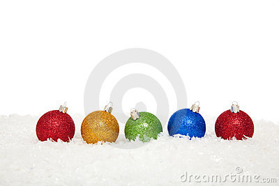Assorted colored christmas ornaments in snow