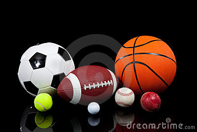 Assorted sports balls on a black background
