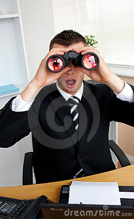 Astonished businessman looking through binoculars