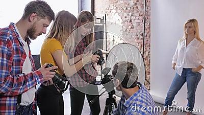 Atelier photo, compagnie de photographes discutent de l'installation d'un appareil photo reflex pendant la formation d'un studio  clips vidéos