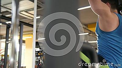 Athlète de jeune homme faisant l'exercice abdominal de barre cabreuse dans le gymnase - concept de forme physique banque de vidéos