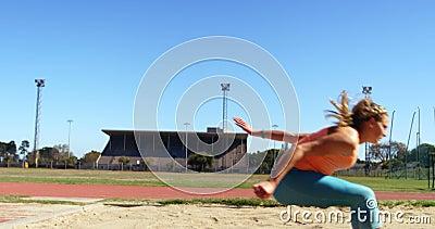Athlète féminin pratiquant le long saut à la rencontre sportive 4k banque de vidéos