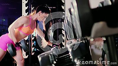Athl?te f?minin faisant l'exercice avec une halt?re dans le gymnase Dans le projecteur clips vidéos