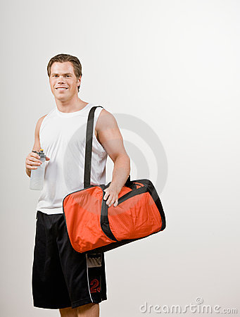 Athlete holding gym bag and water bottle