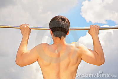 Athlete pull oneself up on sky background