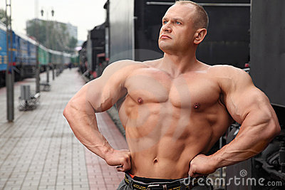 Athlete shows muscles against train