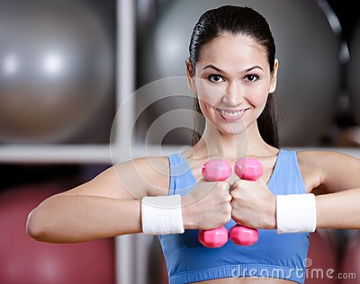 Athlete woman training with dumbbells