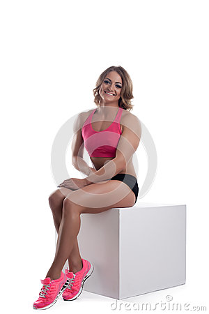Athletic beauty woman with muscle body sit on cube