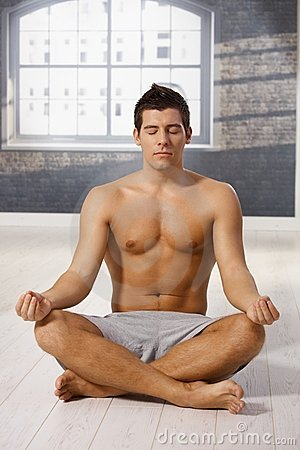 Athletic guy meditating