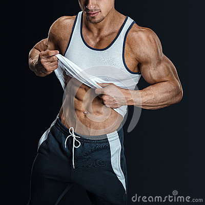 Free Athletic Male Model Posing, Pulling Up Tank Top Stock Images - 57465334
