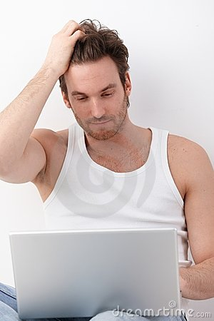 Athletic man browsing internet on laptop