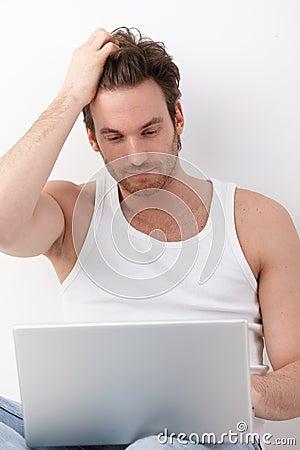 Athletic man browsing internet on laptop