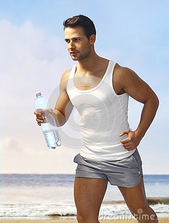 Athletic man jogging on the beach