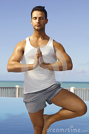 Athletic man practicing yoga outdoors