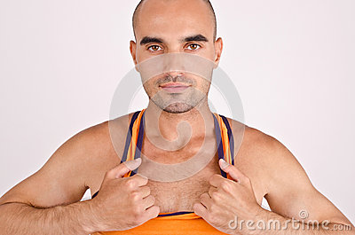 Athletic man pulling his orange tank top.