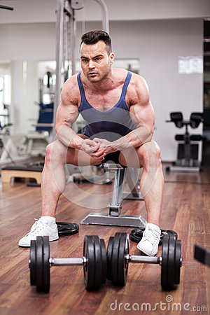 Athletic man resting on a bench at the gym