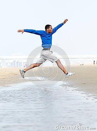 Athletic man running and jumping at beach