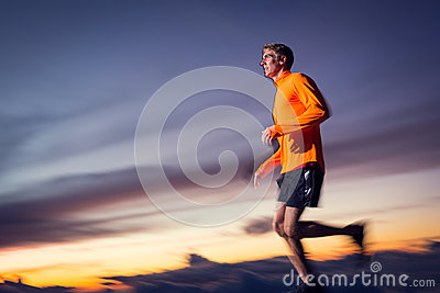 Athletic man running at sunset