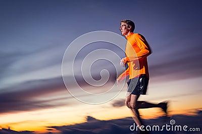 Athletic man running at sunset