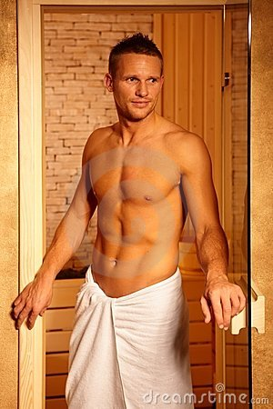 Athletic man at sauna door