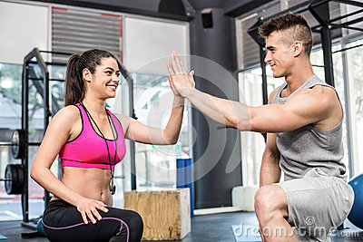 Athletic man and trainer woman giving a high five Stock Photo