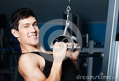 Athletic man works out on fitness gym equipment