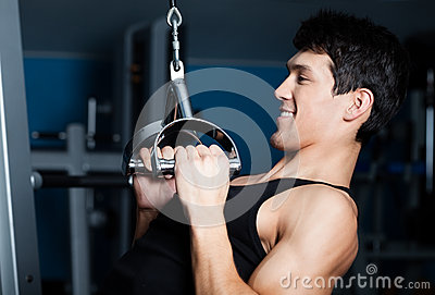 Athletic man works out on training apparatus