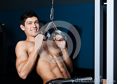 Athletic man works out on training gym equipment