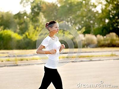 Athletic Runner Training in a park for Marathon. Fitness Girl Ru