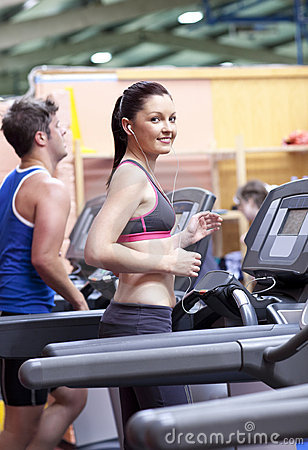 Athletic woman listening to the music on treadmill