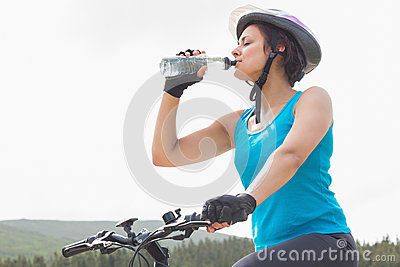 Athletic woman on mountain bike drinking water