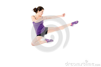 Athletic woman performing a flying side kick