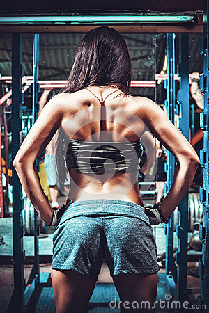 Athletic woman showing muscles of the back