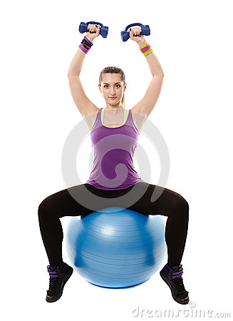 Athletic woman sitting on a ball and working with dumbbells