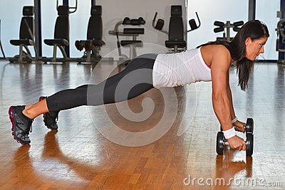 Athletic young lady doing workout in fitness studio