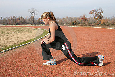 Athletic Young Woman Stretching at the Track