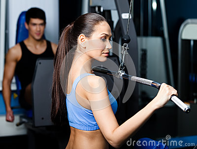 Athletic young woman works out on fitness gym equipment