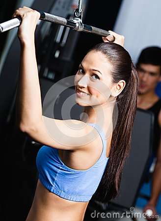 Athletic young woman works out in gym