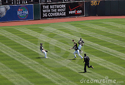 Athletics run down ball in outfield Editorial Stock Image