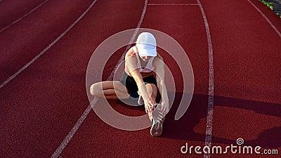 Athletische Frau, die Beine vor Lauf auf Laufbahn ausdehnt stock footage