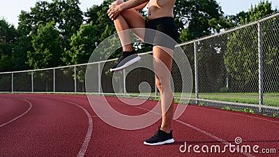 Athletische Frau, die Beine vor Lauf auf Laufbahn ausdehnt stock video