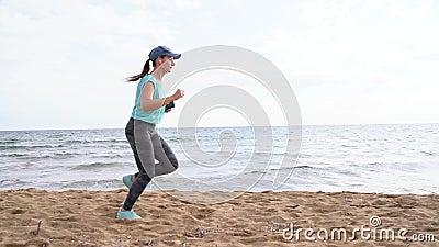 Athletische Frau, die entlang den Strand läuft Video mit verschiedenen Geschwindigkeiten - schnell, normal und langsam stock footage