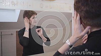 Atirar sobre o ombro de reflexão ao espelho da encantadora senhora morena sênior Mulher caucasiana tocando seu rosto e vídeos de arquivo