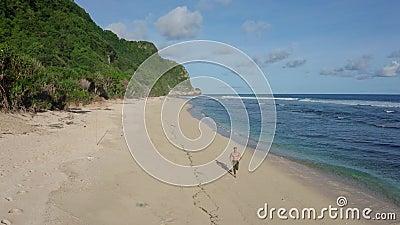 Atleta aérea corre sozinho na praia arenosa, no oceano, nas montanhas ao fundo filme