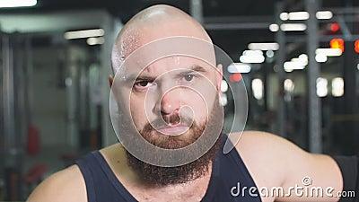 Atleta ativo e bonito que fica perto da barra de metal após treinamento em garagem subterrânea vídeos de arquivo