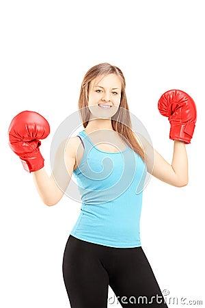 Atleta de sexo femenino feliz que lleva guantes y gesticular de boxeo rojos