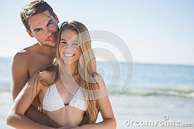 Atletisch paar die bij camera en het omhelzen glimlachen