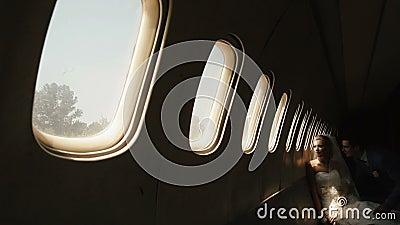 Atmosfera romântica A noiva loura bonita está olhando o lance a janela no avião quando o noivo a beijar dentro filme